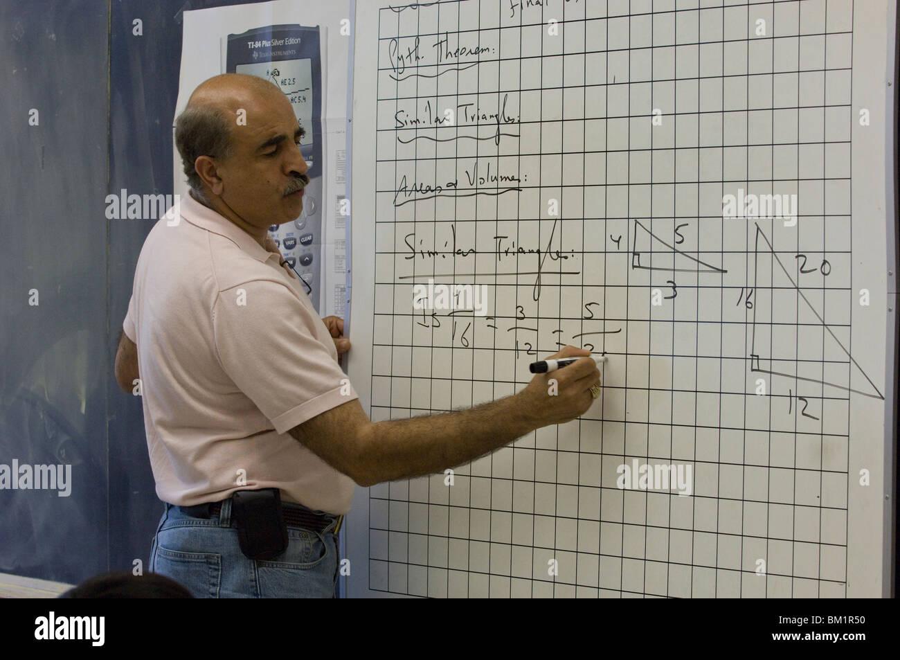 Hispanic male high school geometry teacher write problem on white ...