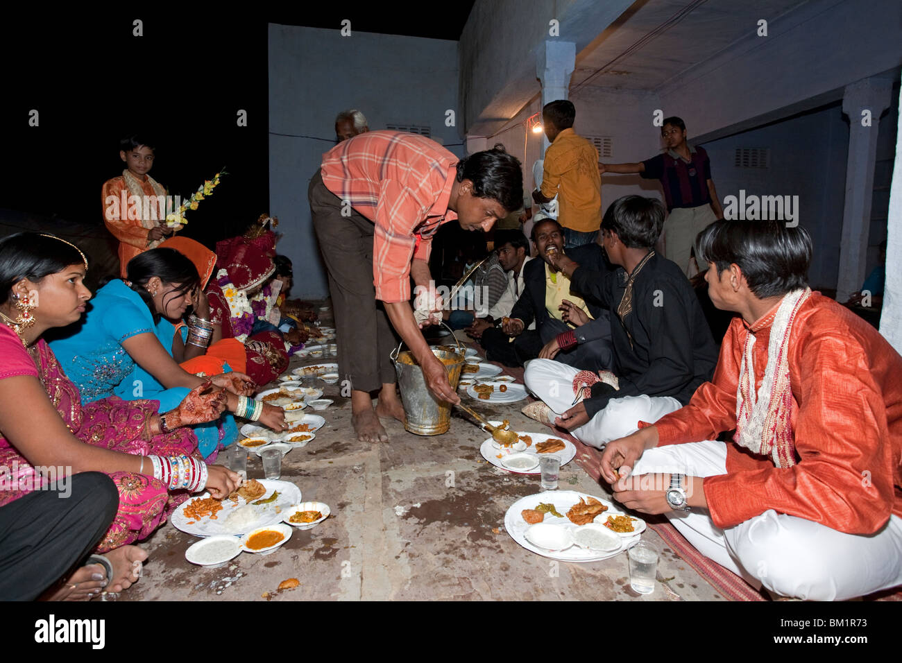 indian people eating a traditional thali wedding
