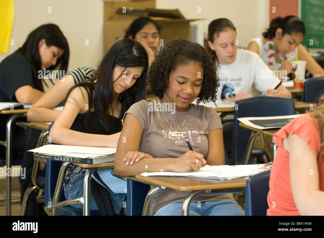 Multi-ethnic group of high school students take notes in ...