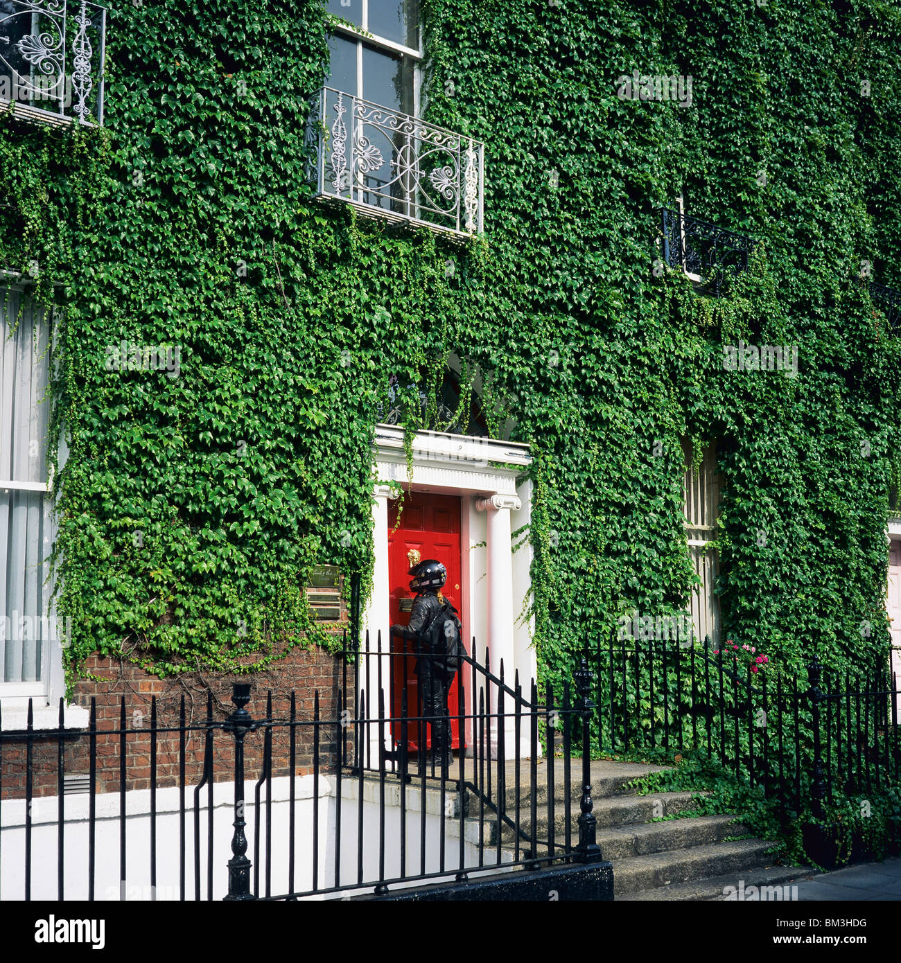 GEORGIAN IVY-COVERED HOUSE AND COURIER AT RED FRONT DOOR DUBLIN IRELAND