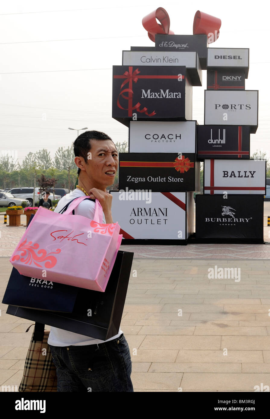 coach store premium outlets 1xrl  Chinese man carrying shopping bags at Beijing Scitech Premium Outlet Mall  Beijing, China 15-May-2010