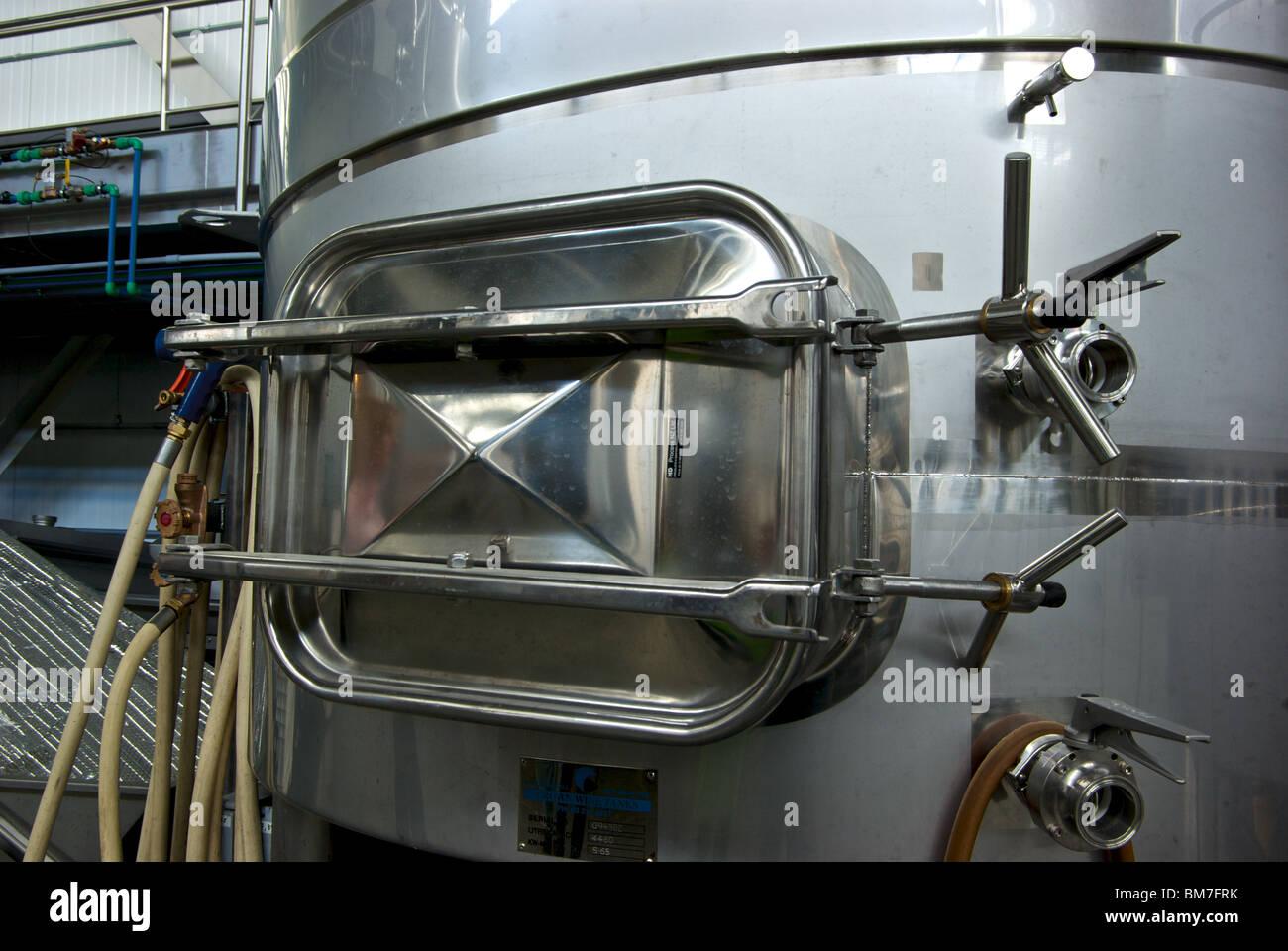 Heavy duty hatch door at bottom of stainless steel fermentation tanks in Tantalus Winery cellar & Heavy duty hatch door at bottom of stainless steel fermentation ...