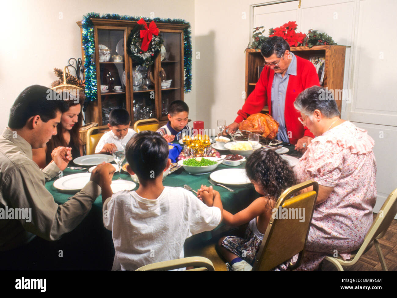 Hispanic Family Gives Thanks Say Grace Before Christmas Turkey Dinner Meal Love Touch Share Eat Dine Holiday Event Special