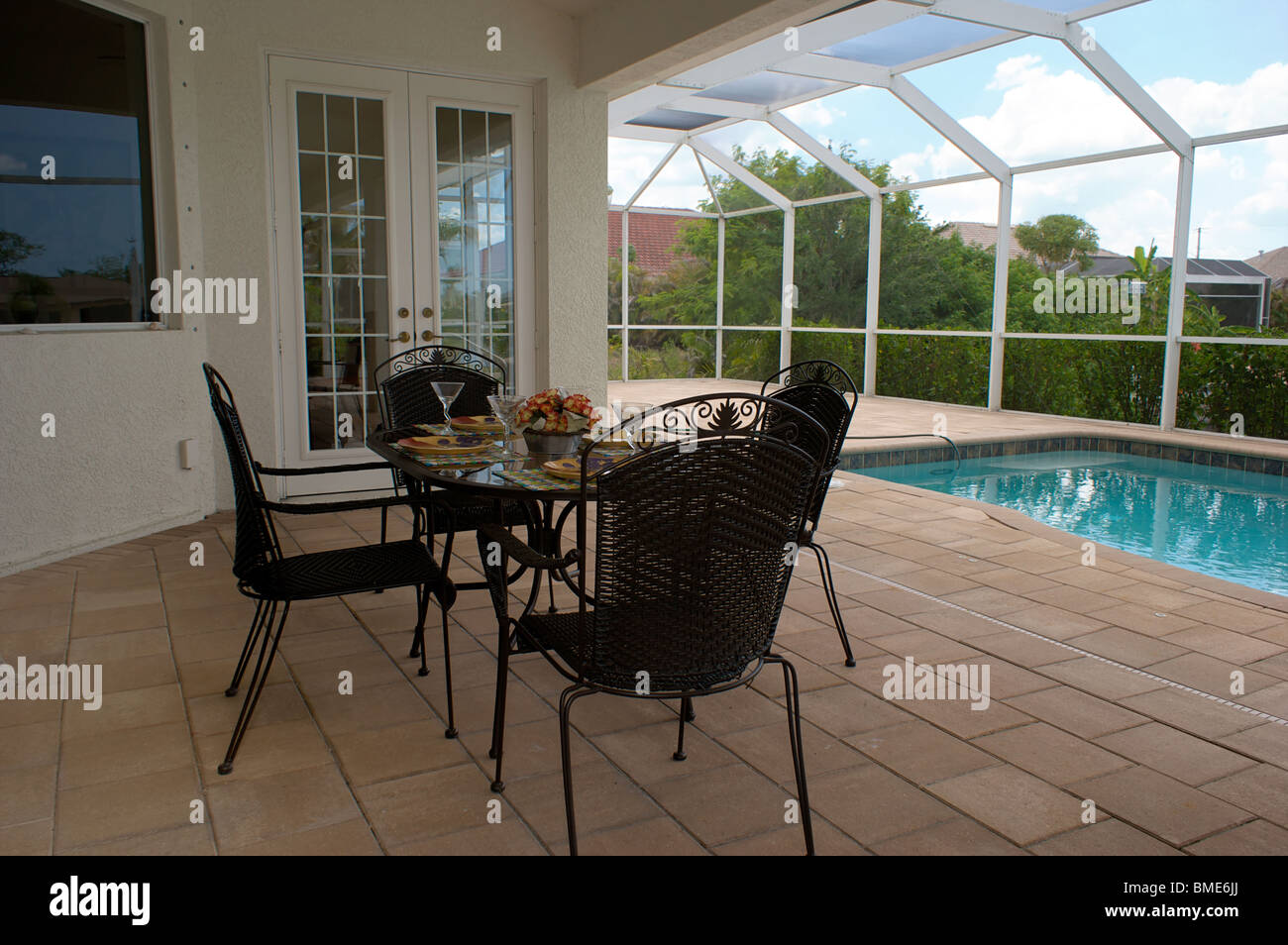 Stock Photo   A Table Is Set For Dinner On An Outside Patio Or Lanai With  Swimming Pool In Background, The Patio Is Screened In