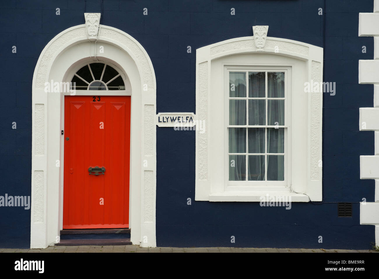 Red Painted Door In A Georgian Arched Doorway On A Blue House, Aberaeron,  Ceredigion, West Wales UK