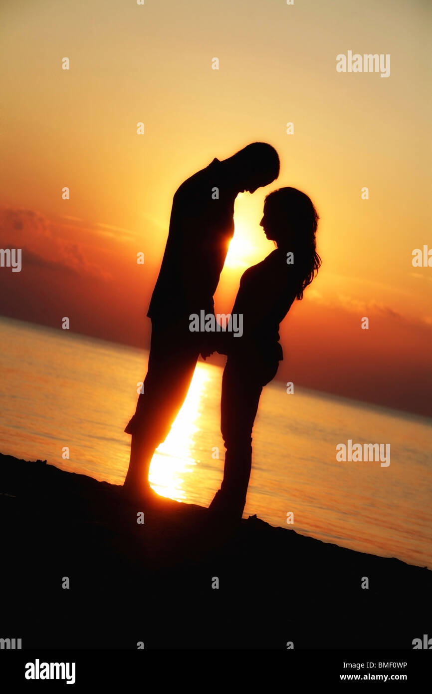 Silhouette Of A Couple Holding Hands On Beach At Sunset Stock ... for Couple Holding Hands Silhouette Sunset  5lpkxo