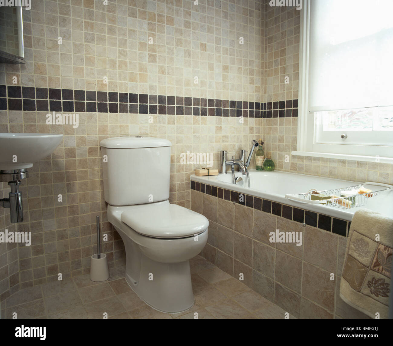 Toilet beside bath with tiled surround in modern beige tiled ...