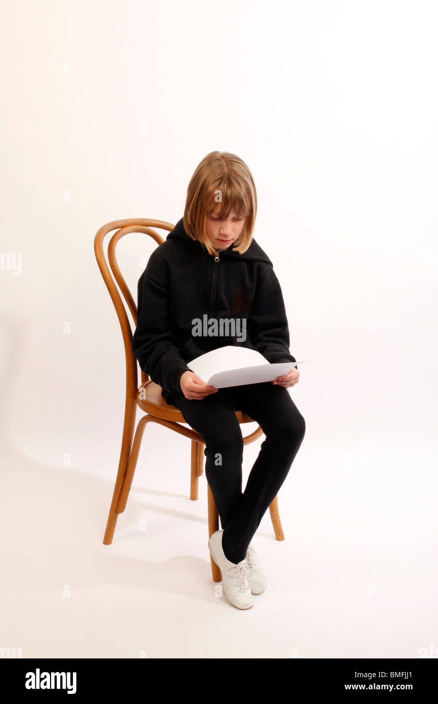 Black child sitting in chair - Stock Photo Child Seated On A Wooden Chair Dressed In Black And Reading A Piece Of Paper Showing Exam Results