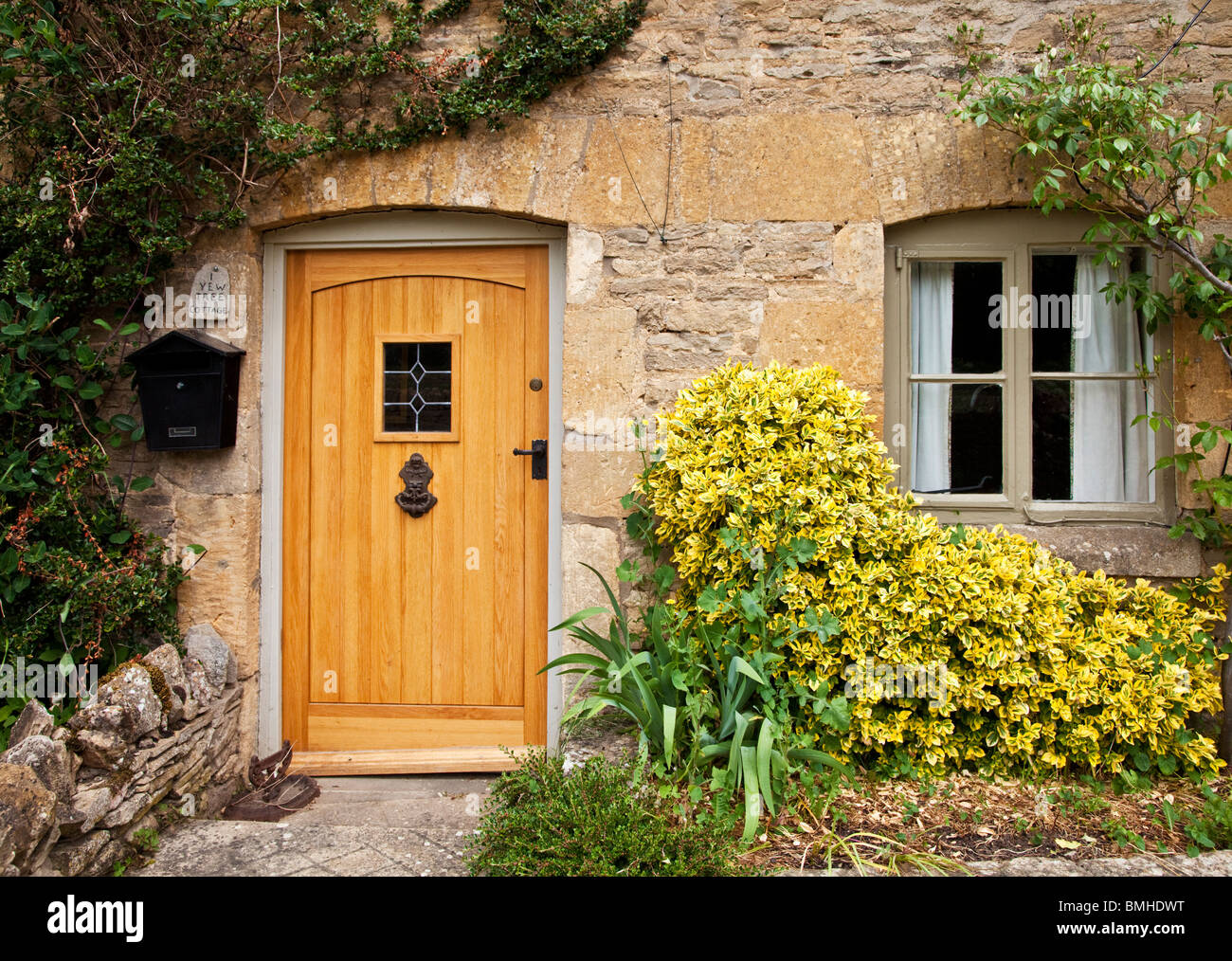 Wooden front door and window on a typical cotswold stone for Door of stone