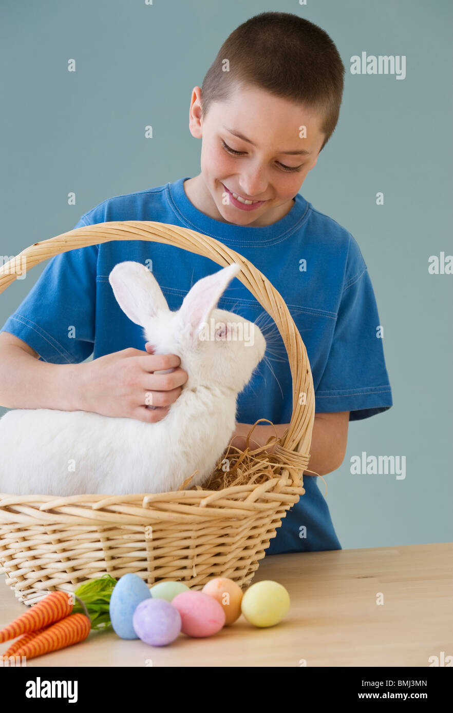 Young boy petting a rabbit in easter basket stock photo royalty stock photo young boy petting a rabbit in easter basket negle Gallery
