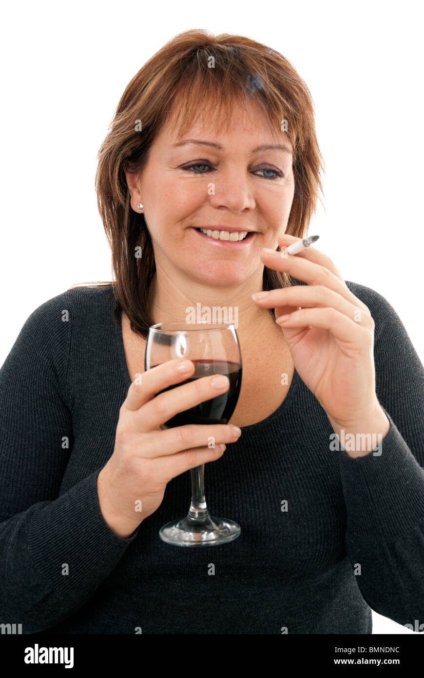 Woman drinking a glass of wine and smoking a cigarette ...