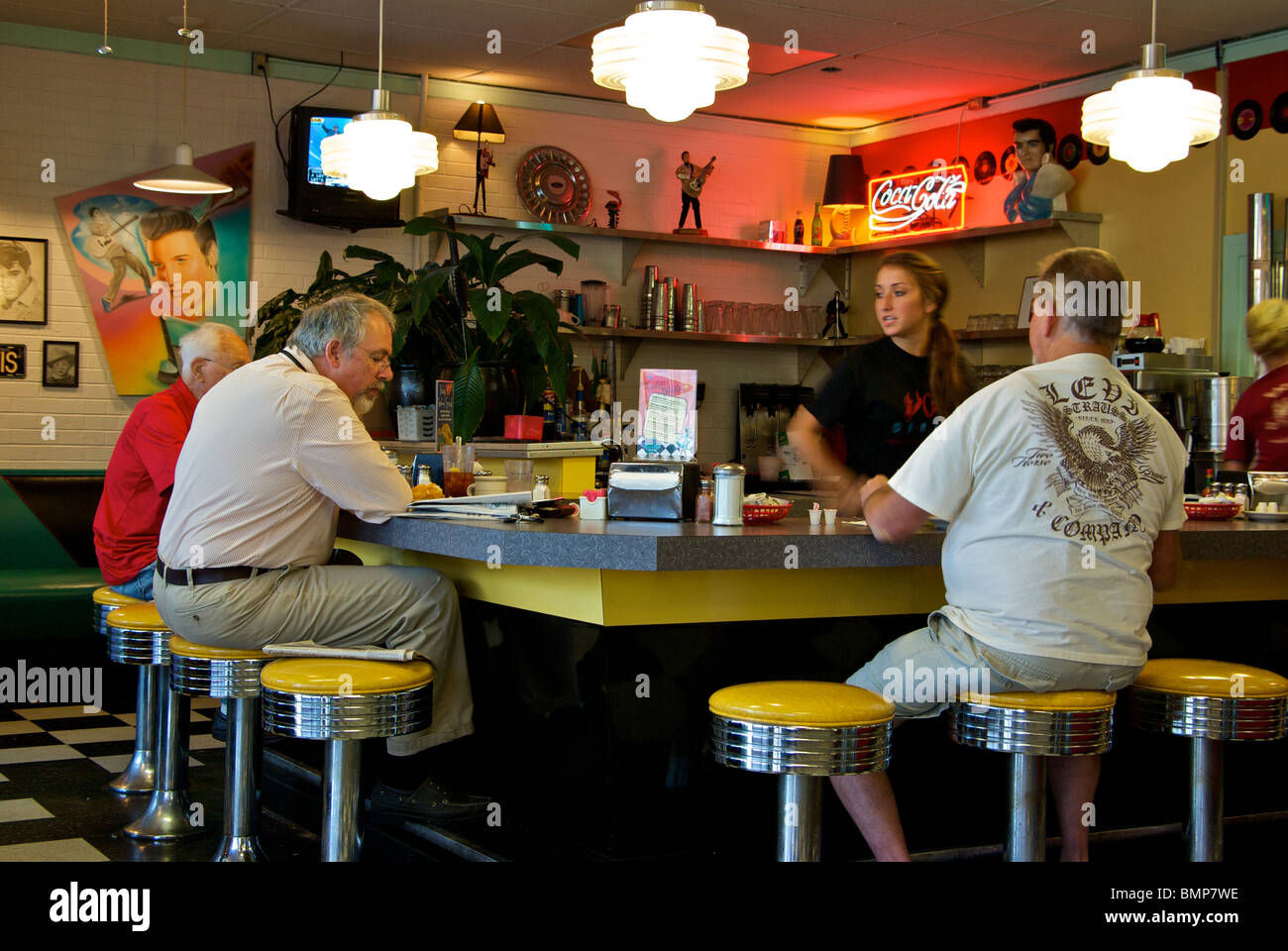Patrons Sitting On Chrome Trimmed Stools At Cafe Bar