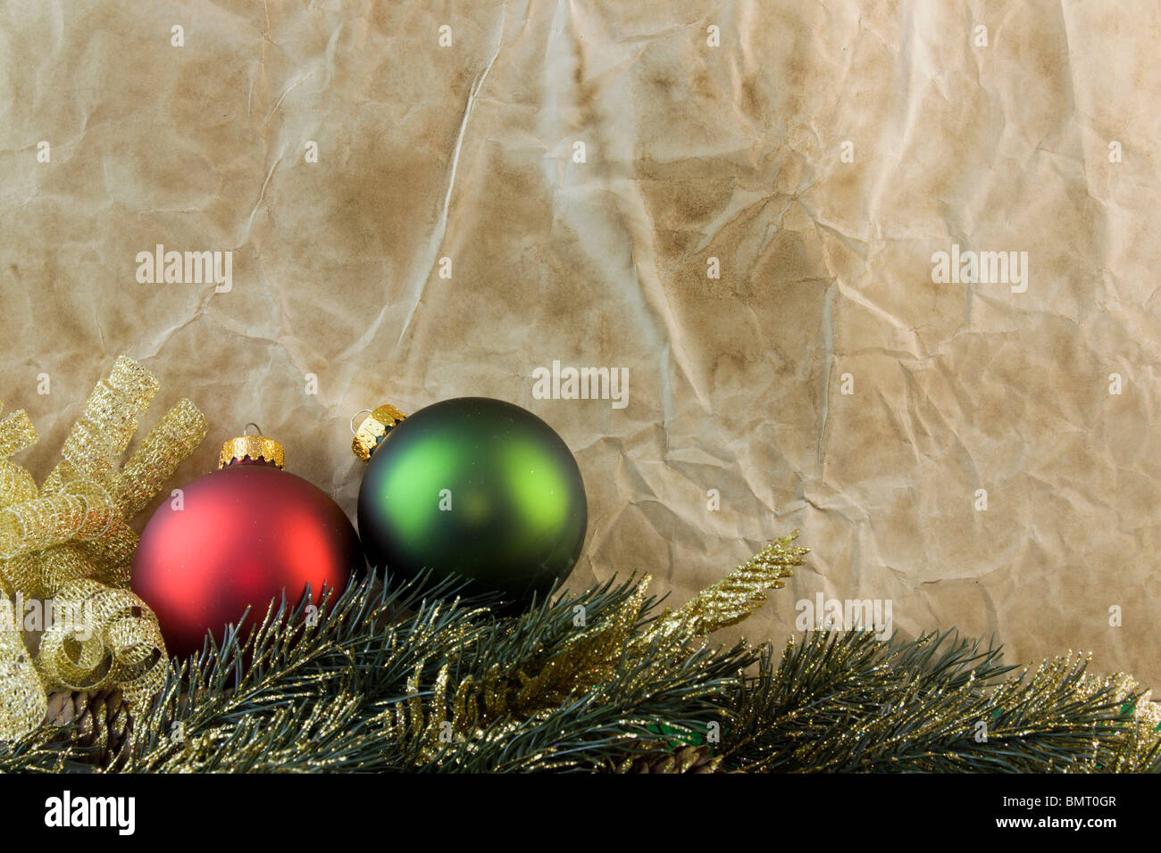 red and green christmas baubles gold flecked fir branch on old fashioned antique paper with copyspace - Old Fashioned Paper Christmas Decorations