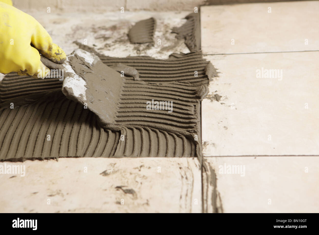 Tiler installing ceramic tiles on a floor using notched trowel tiler installing ceramic tiles on a floor using notched trowel dailygadgetfo Image collections