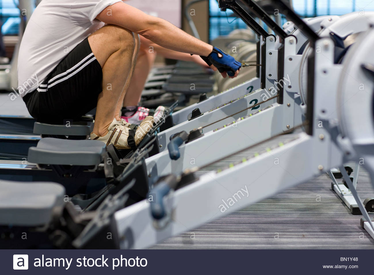 man-working-out-on-rowing-machine-in-hea