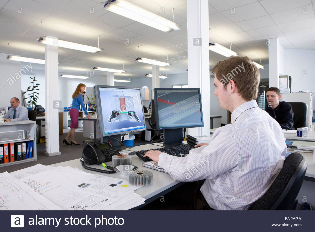 CAD designer working at computer monitors in office Stock Photo ...