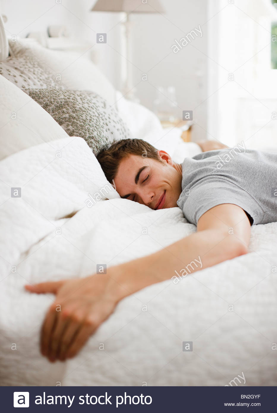 happy man laying on bed stock photo, royalty free image: 30175363