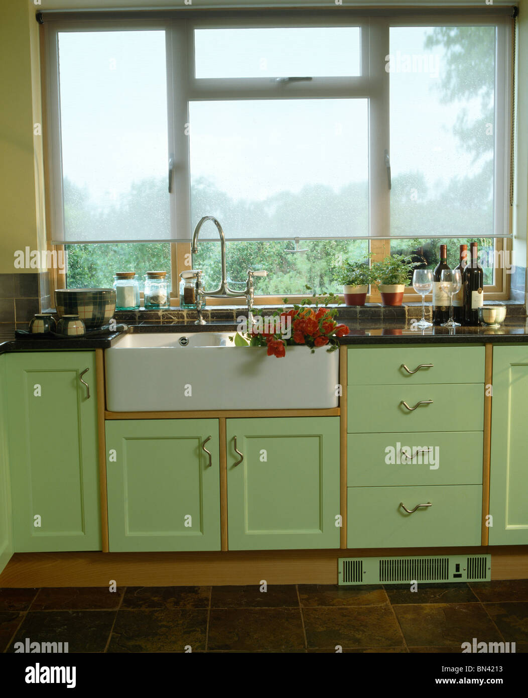 Green country kitchen - Stock Photo White Blind On Window Above Belfast Sink In Country Kitchen With Pale Green Fitted Units