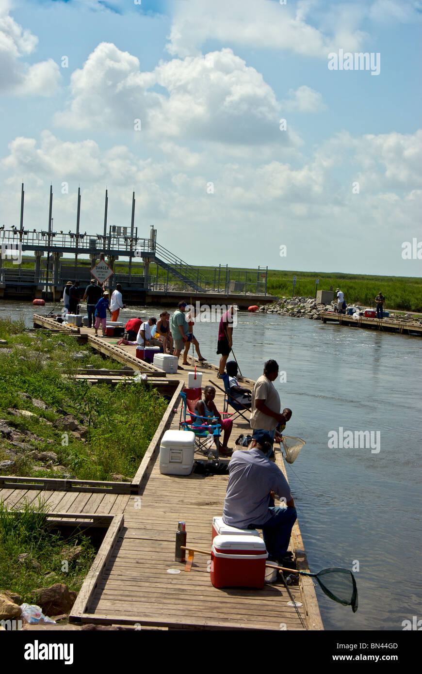 Families fishing and crabbing at a recreation dock along for Buy louisiana fishing license online
