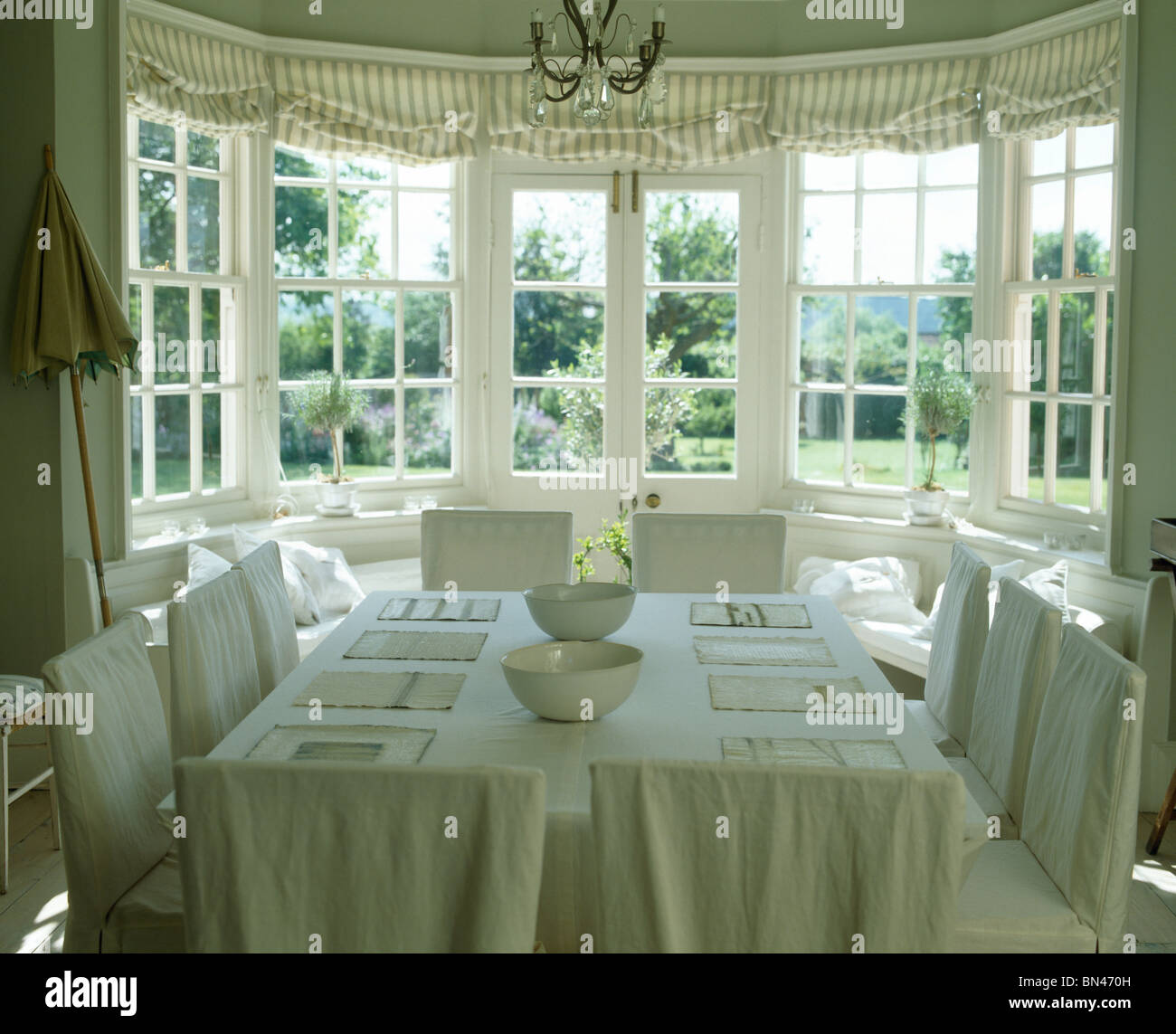 Cream Slip Covers On Chairs In Country Dining Room With Linen Tablecloth Table Front Of Bay Window Striped Blinds