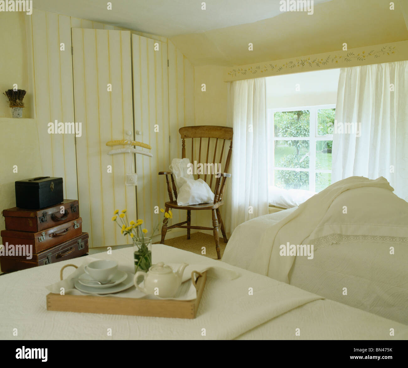 Stock Photo   Teapot and cup on tray on bed in cream country bedroom with  white curtains on window and yellow stripes painted on wardrobe door. Teapot and cup on tray on bed in cream country bedroom with white