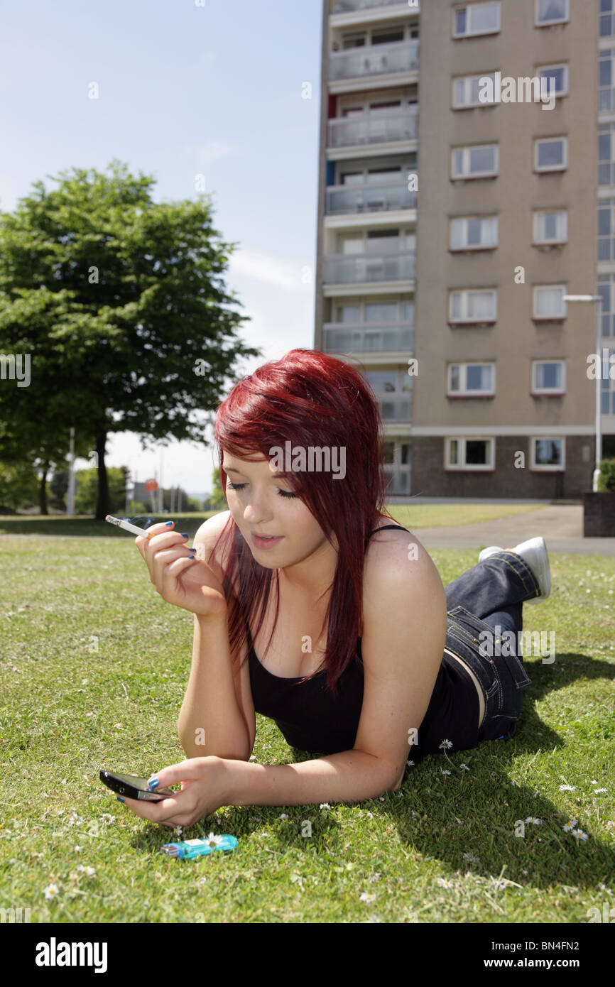 Mattress For Bad Back >> Teenage girl lying down smoking a cigarette and holding a ...