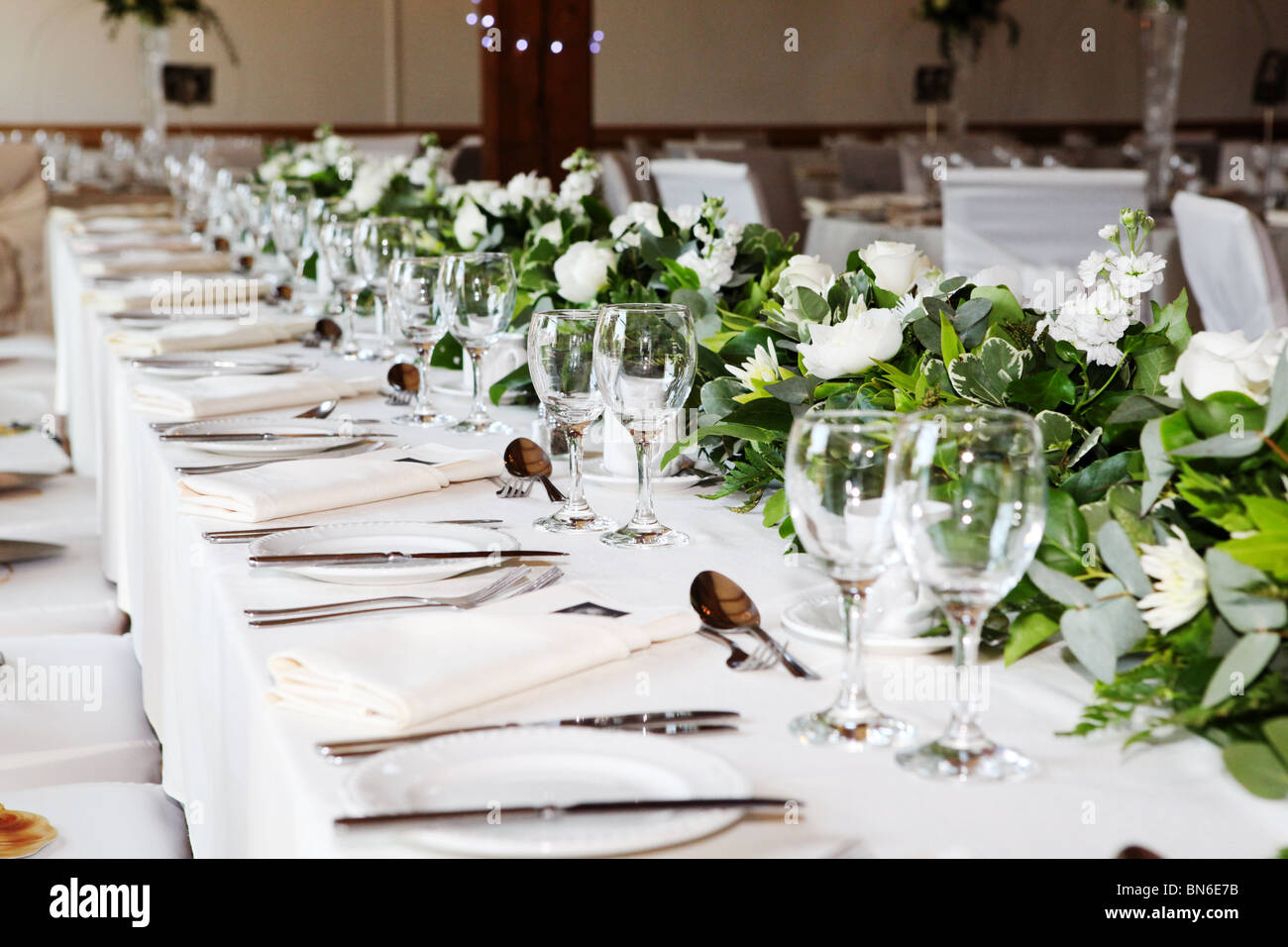 wedding flowers wedding breakfast reception top table laid up and decorated with flowers for a wedding day meal