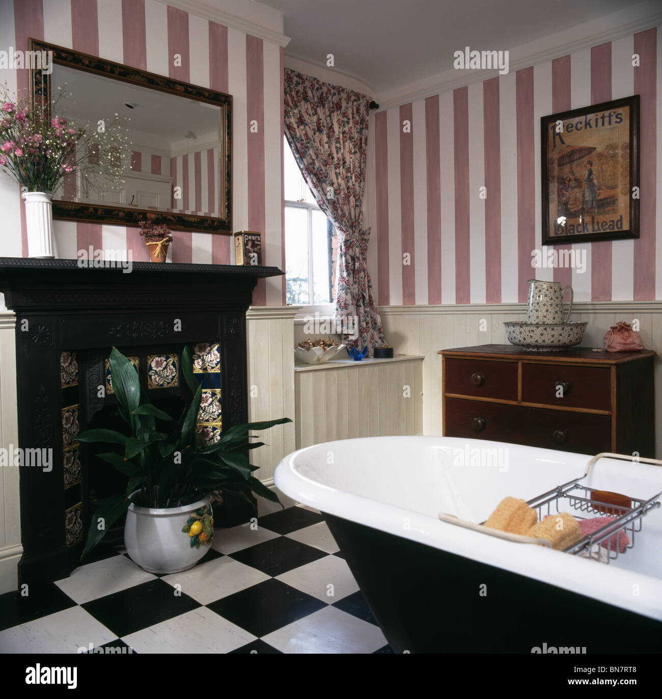 Black white and pink bathroom - Pink Striped Wallpaper And Roll Top Bath In Country Bathroom With Black Cast Iron Fireplace And Black White Vinyl Flooring