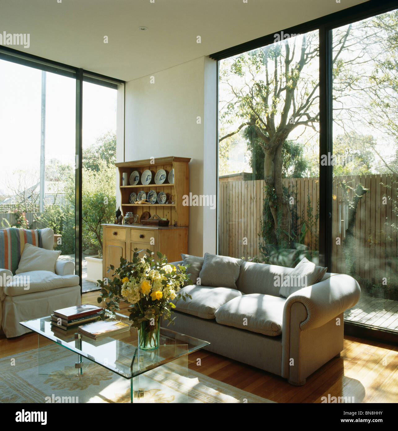 Grey Sofa In Front Of Patio Doors In Modern White Living Room Extension  With Glass Coffee Table And Pine Dresser
