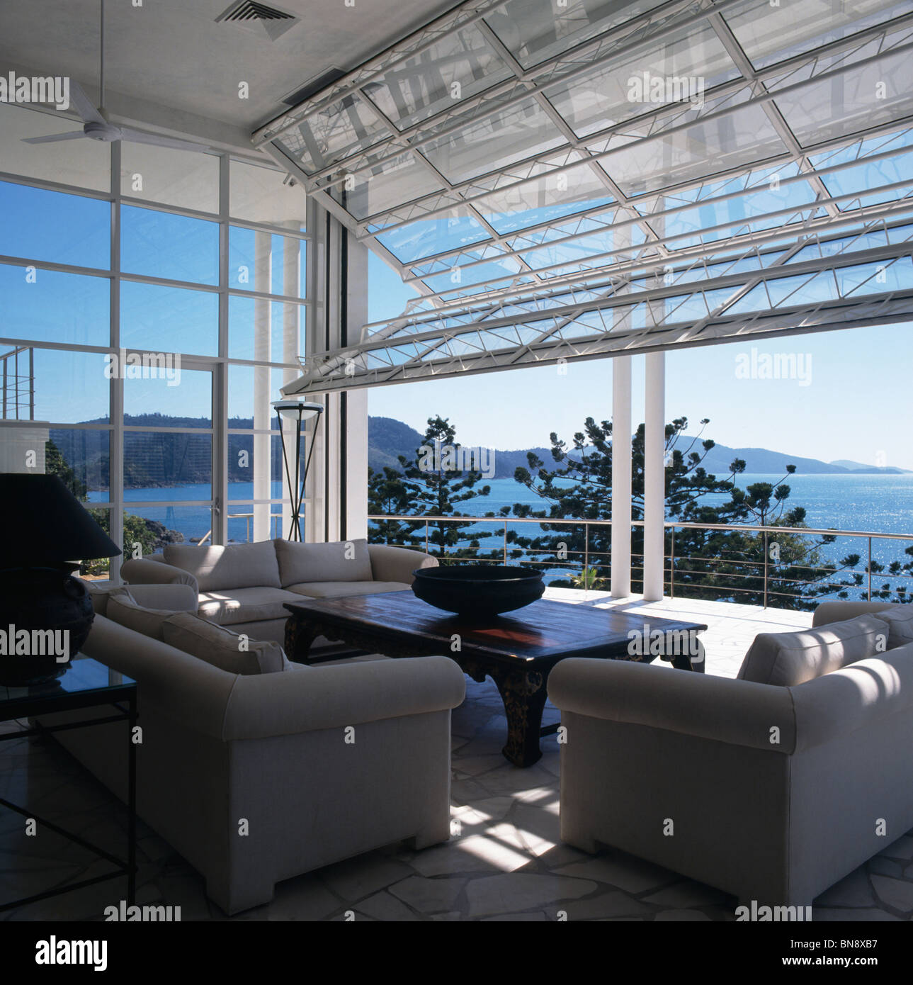 view of the ocean from modern coastal living room with gray sofas stock photo view of the ocean from modern coastal living room with gray sofas and cantilevered fold up glass doors
