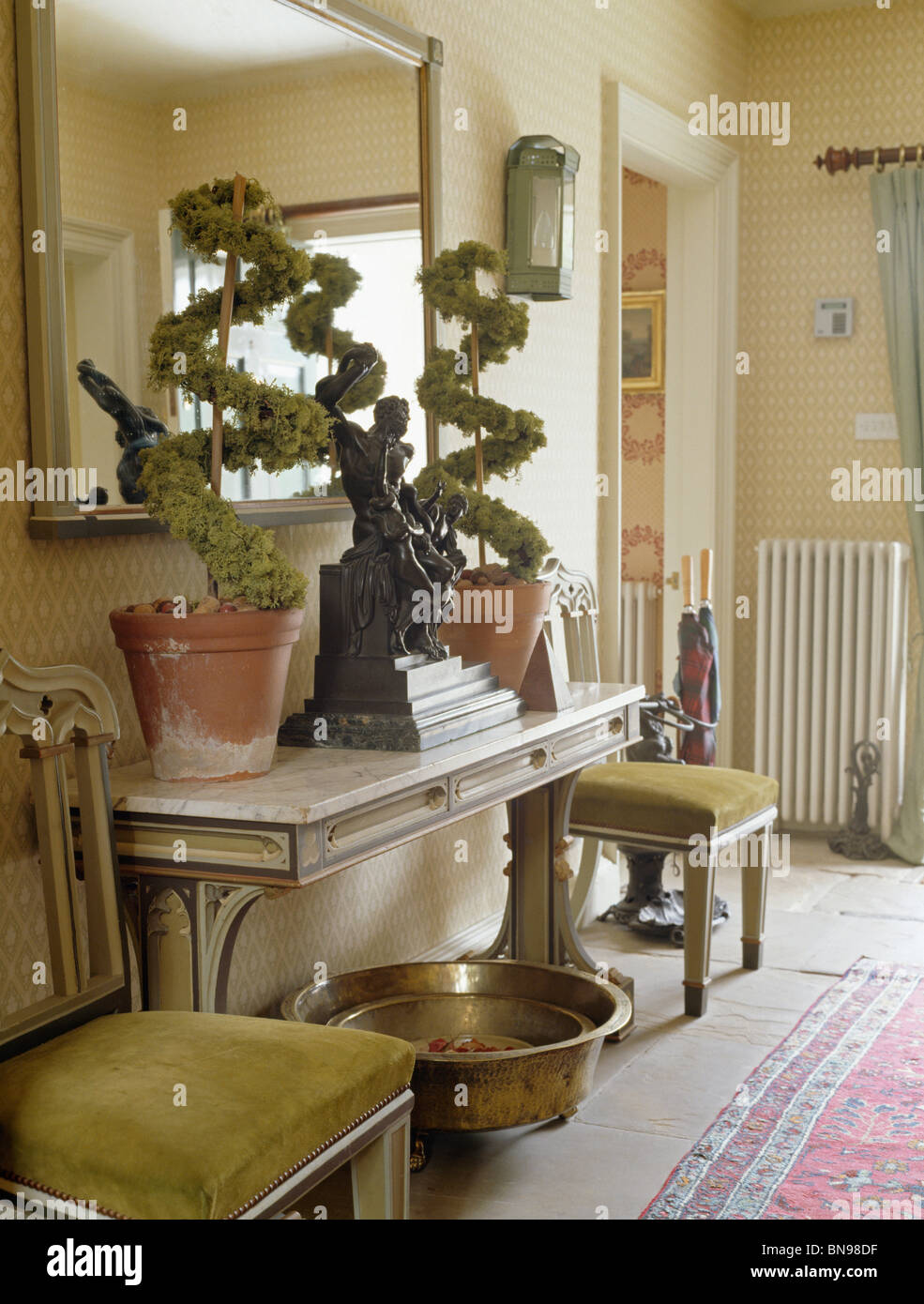 Large mirror above topiary plants on console table in cream