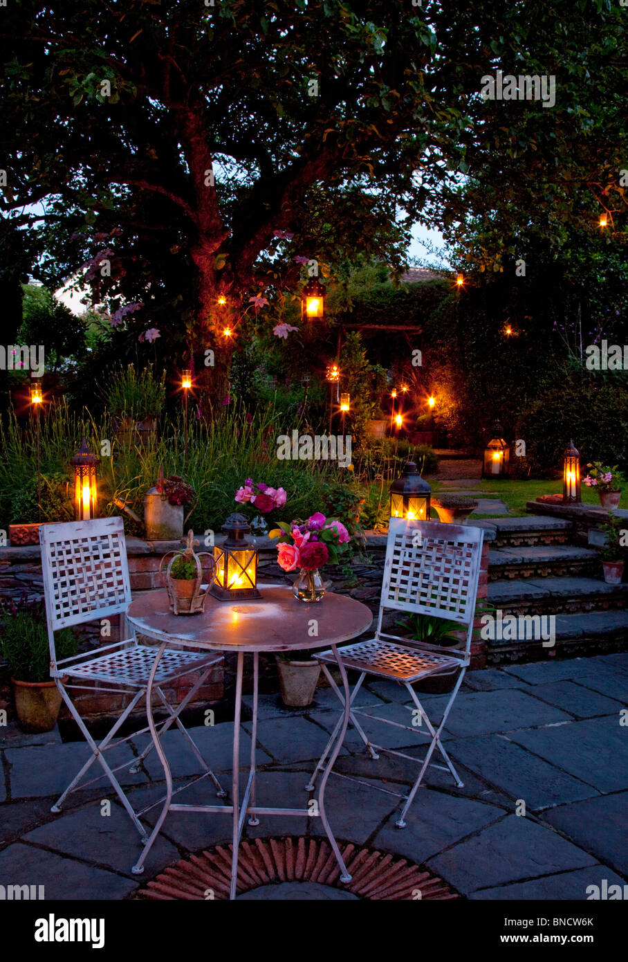 High Quality Metal Table And Chairs On Patio With Candles And Lanterns In Garden At Night