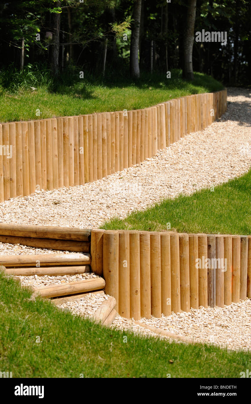 Gravel Pathway With Wooden Fence Posts Used As A Retaining