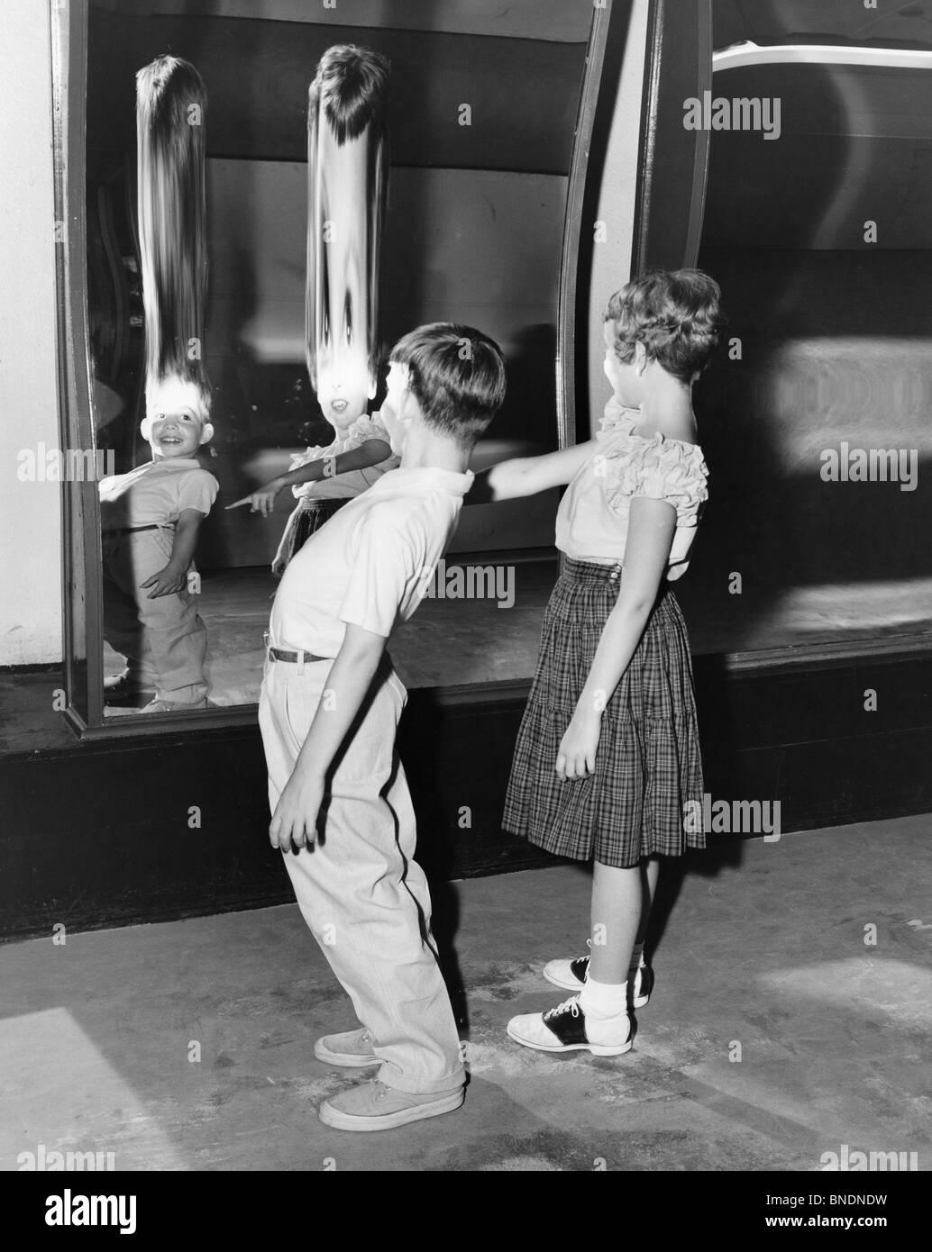 Profile Of Boy And Girl Looking In Fun House Mirror Stock