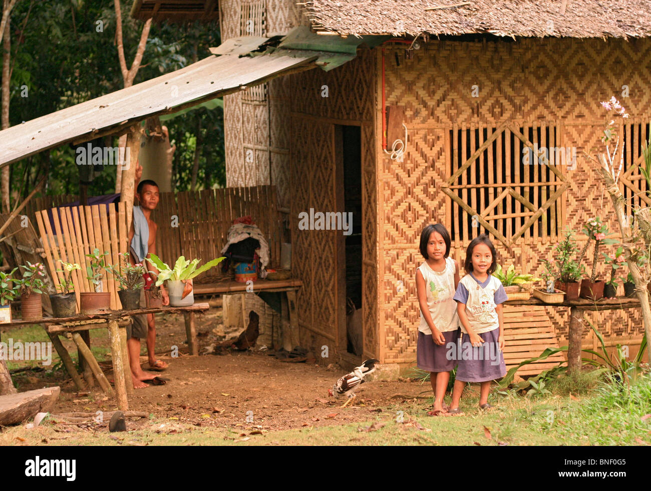 Man And Two Young Girls Standing Outside Their Home A