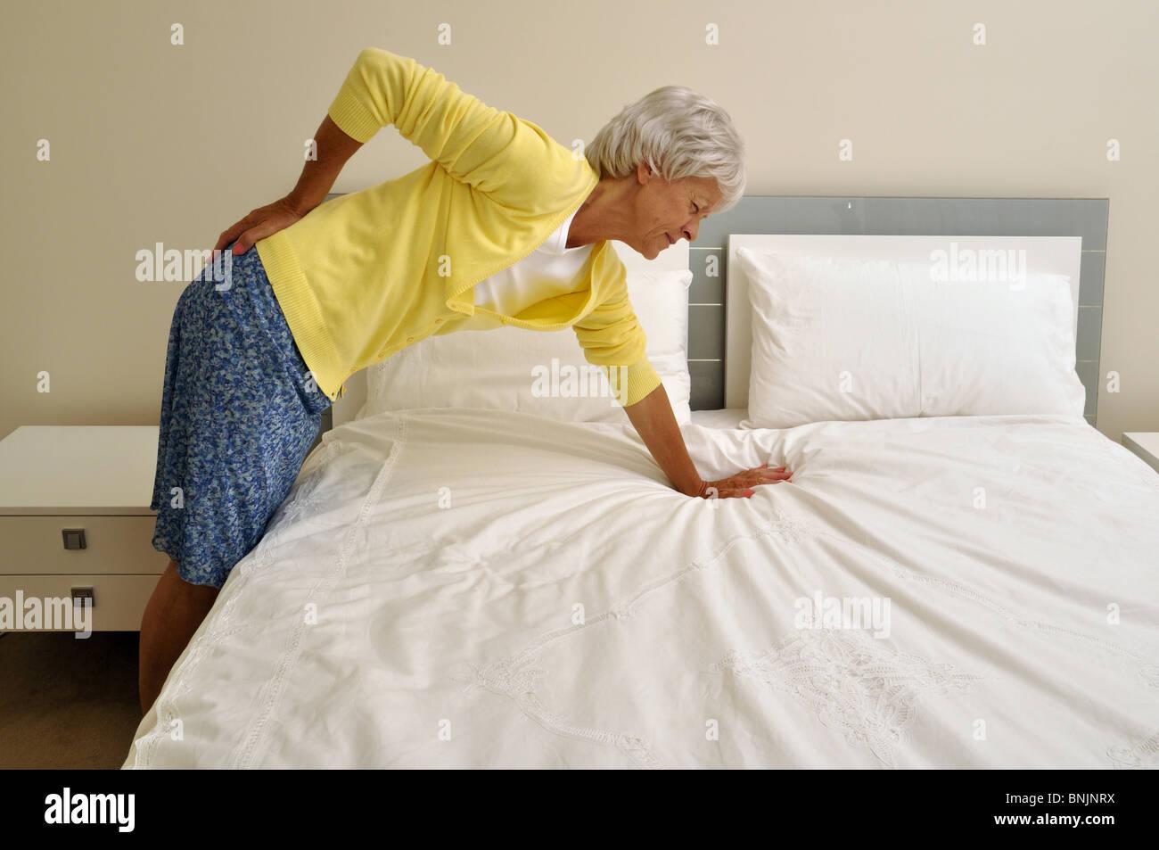 back pain pensioner senior old woman mature lumbago hurt pain bedroom stock photo royalty free. Black Bedroom Furniture Sets. Home Design Ideas