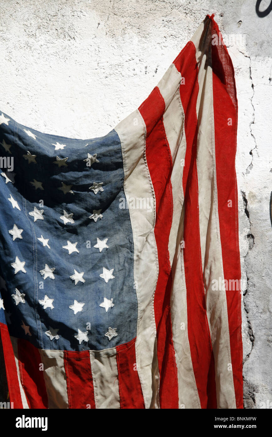 one old american flag hanging on wall outside in sun stock. Black Bedroom Furniture Sets. Home Design Ideas
