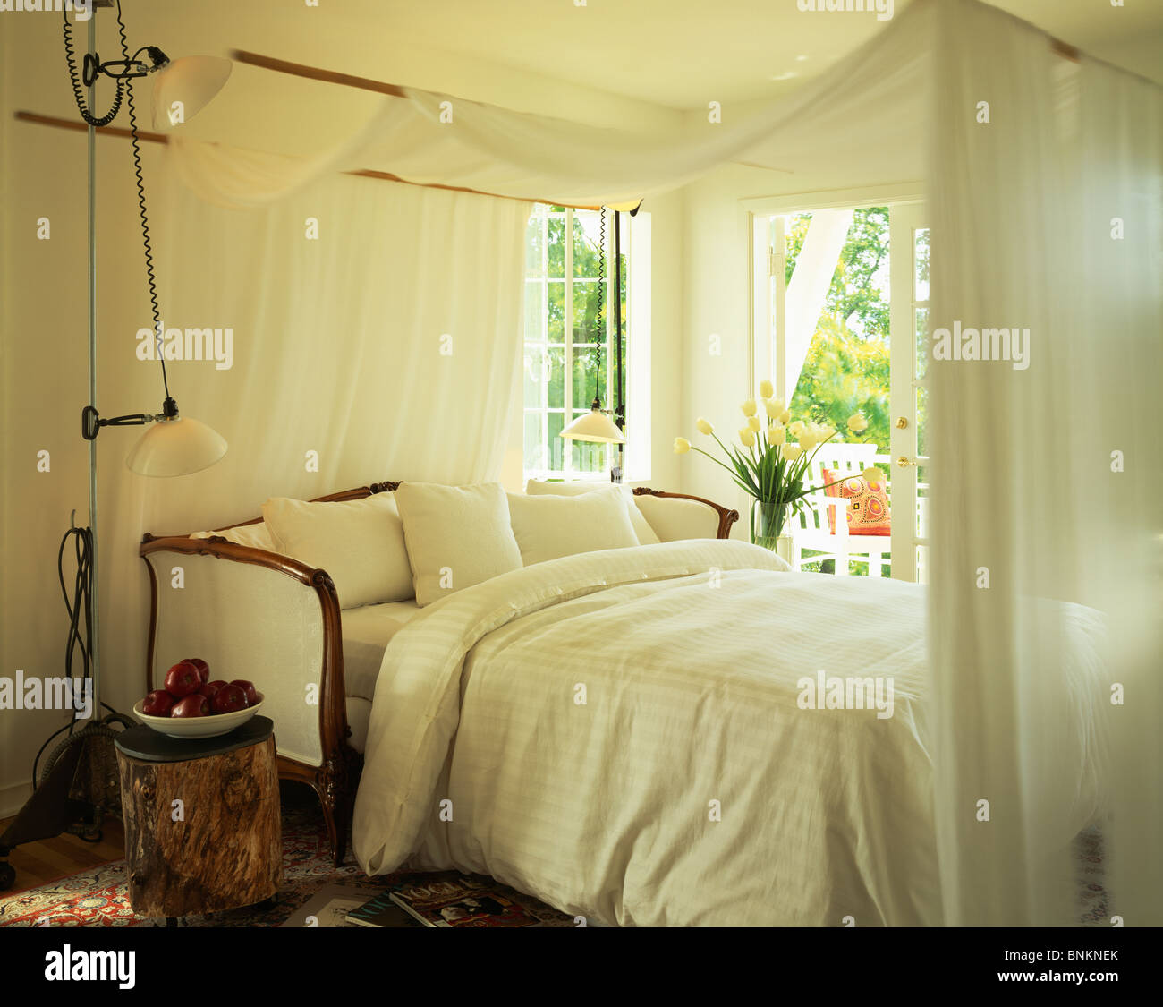 White voile canopy above sofa-bed with white bedlinen in white bedroom with tall l& beside bed & White voile canopy above sofa-bed with white bedlinen in white ...