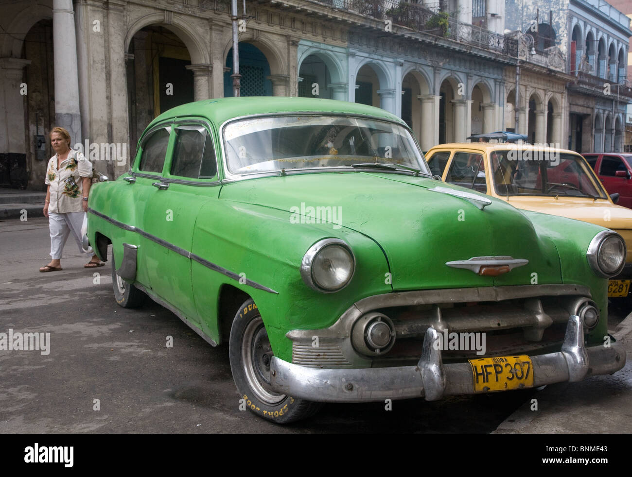Old green chevrolet car in front of colonial buildings in old ...