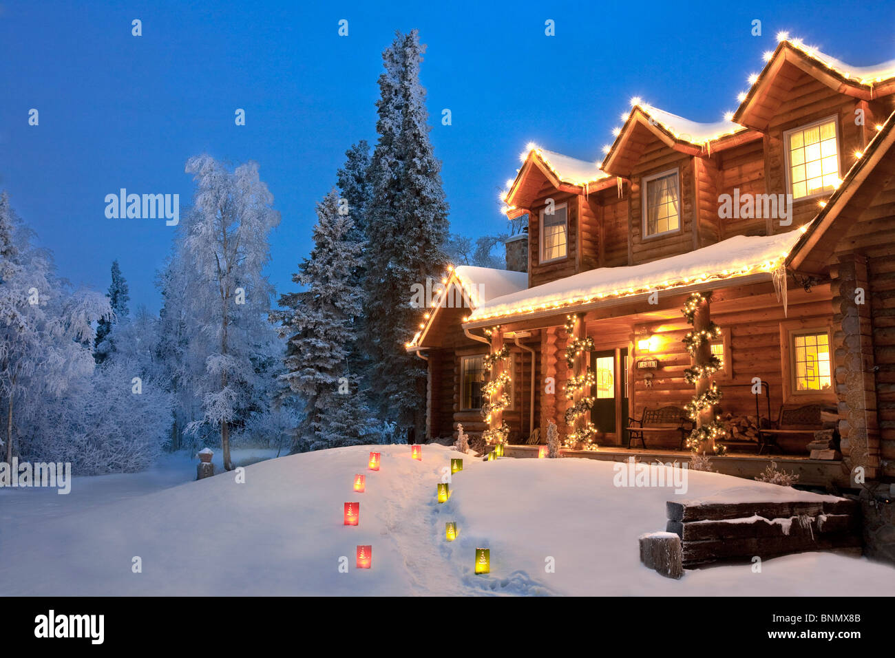 log home decorated with christmas lights and luminaries on the stock