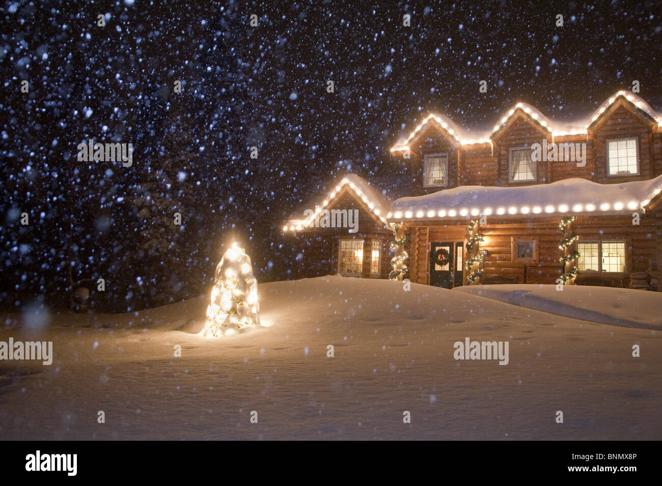 Log home decorated with Christmas lights with snow falling ...