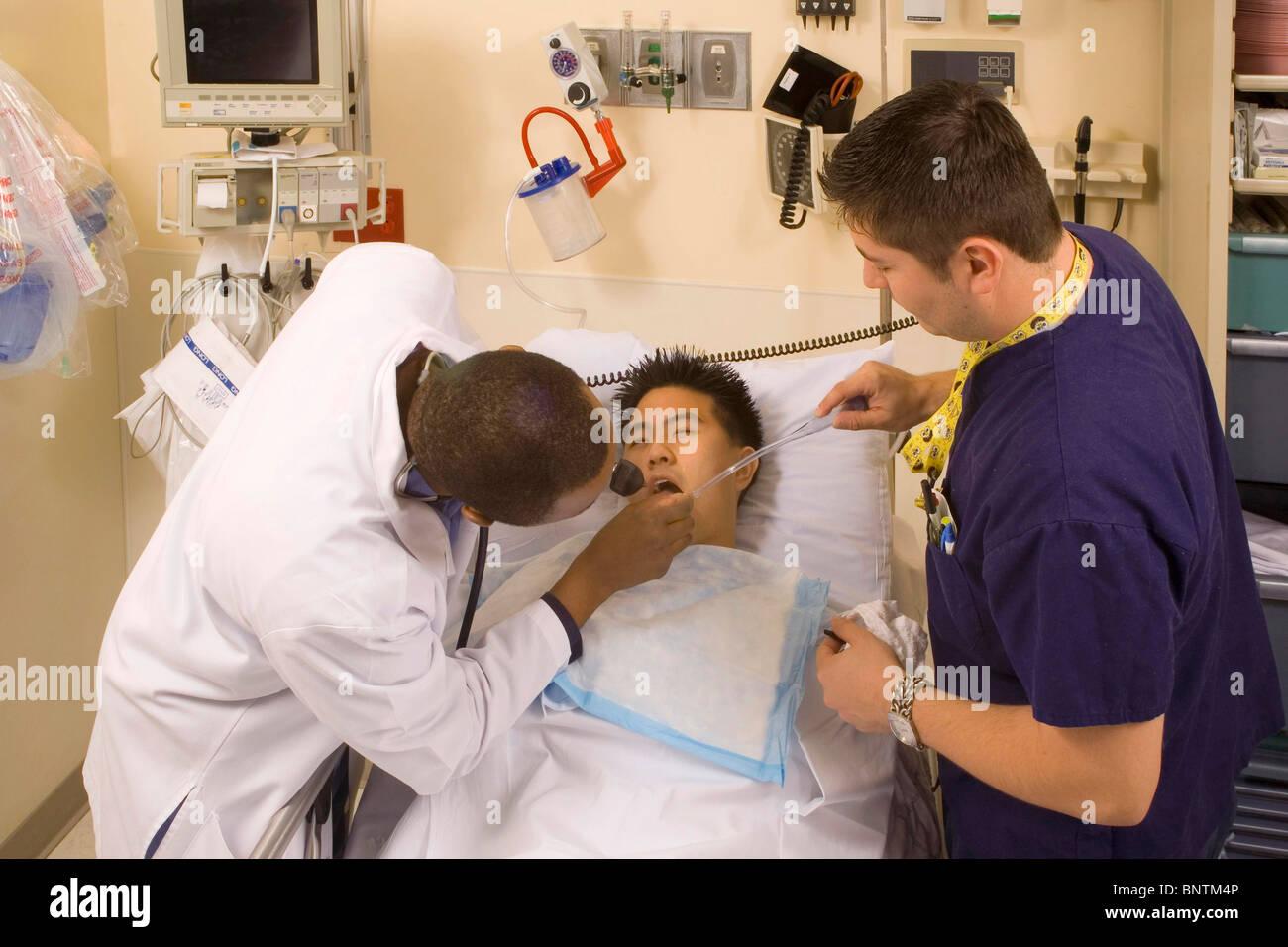 Emergency room physician (left) examines teen drug overdose victim ...