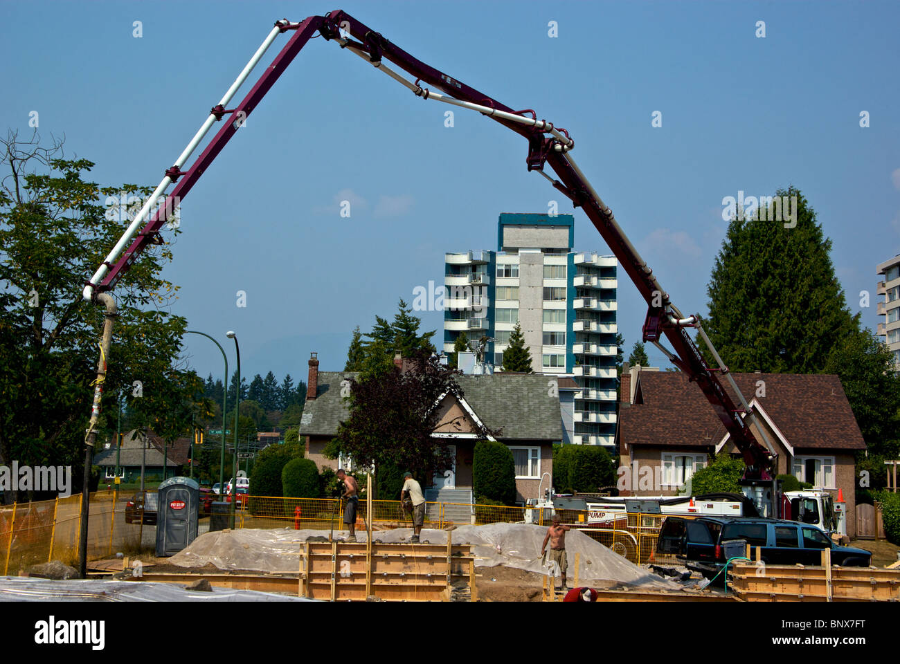 Concrete pumper truck uses extra long hydraulic arm hose pipe to reach foundation forms at house construction site