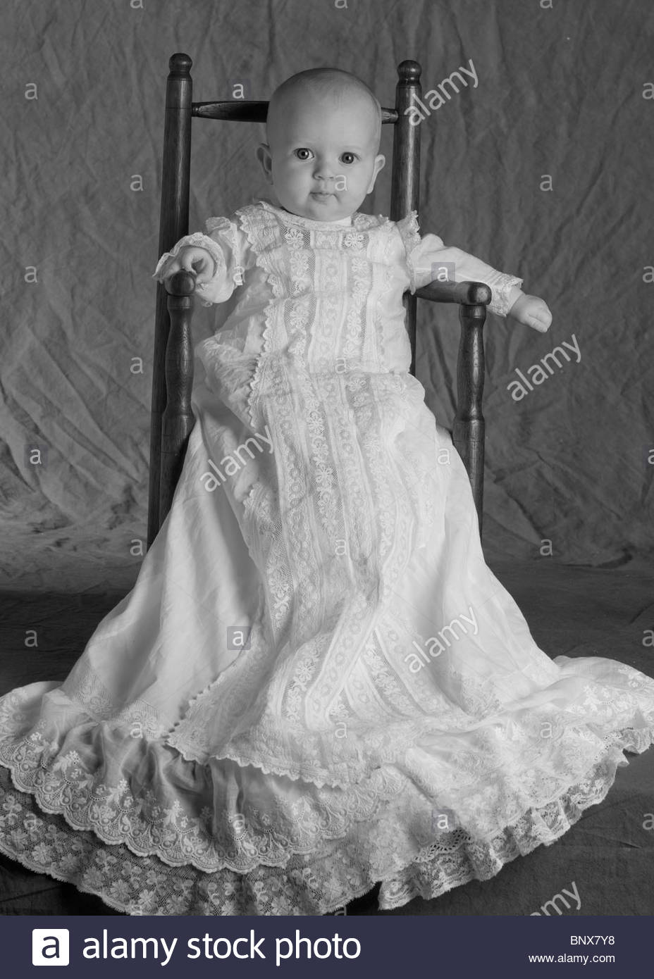 Black child sitting in chair - Baby Girl Sitting In Antique Chair In Her Christening Gown Stock Image