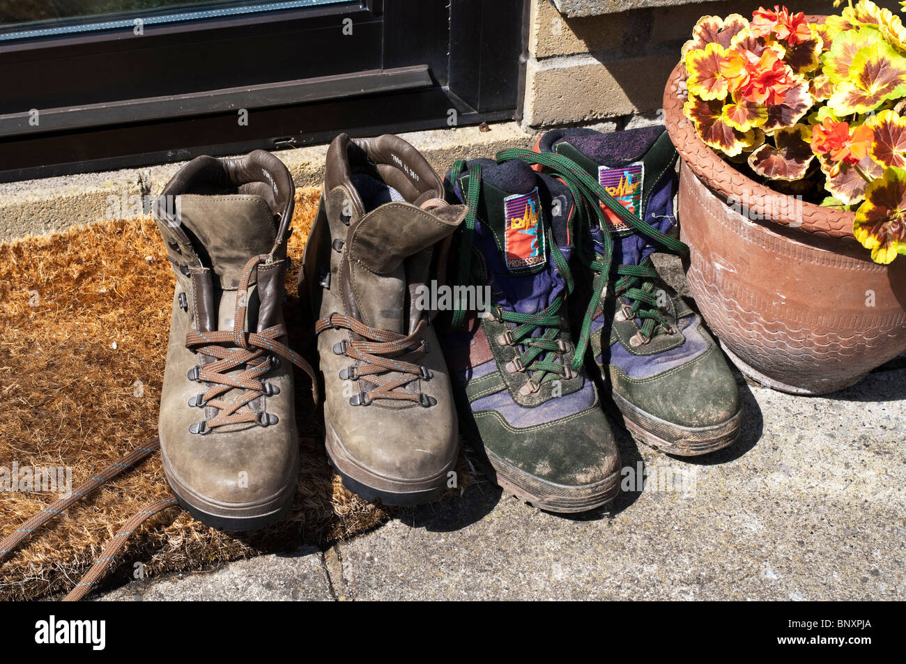 Old used hiking boots on the doorstep outside in the sun Stock ...