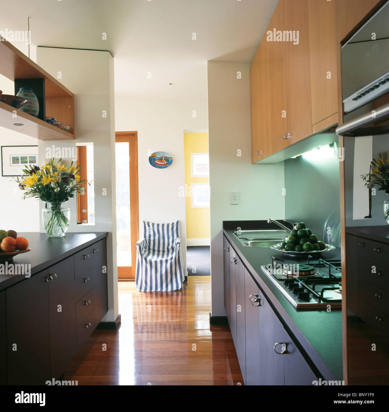 lighting for galley kitchen. Lighting Above Hob In Fitted Unit Open-plan Galley Kitchen With Wooden Flooring And View Of Chair Striped Loose-cover For
