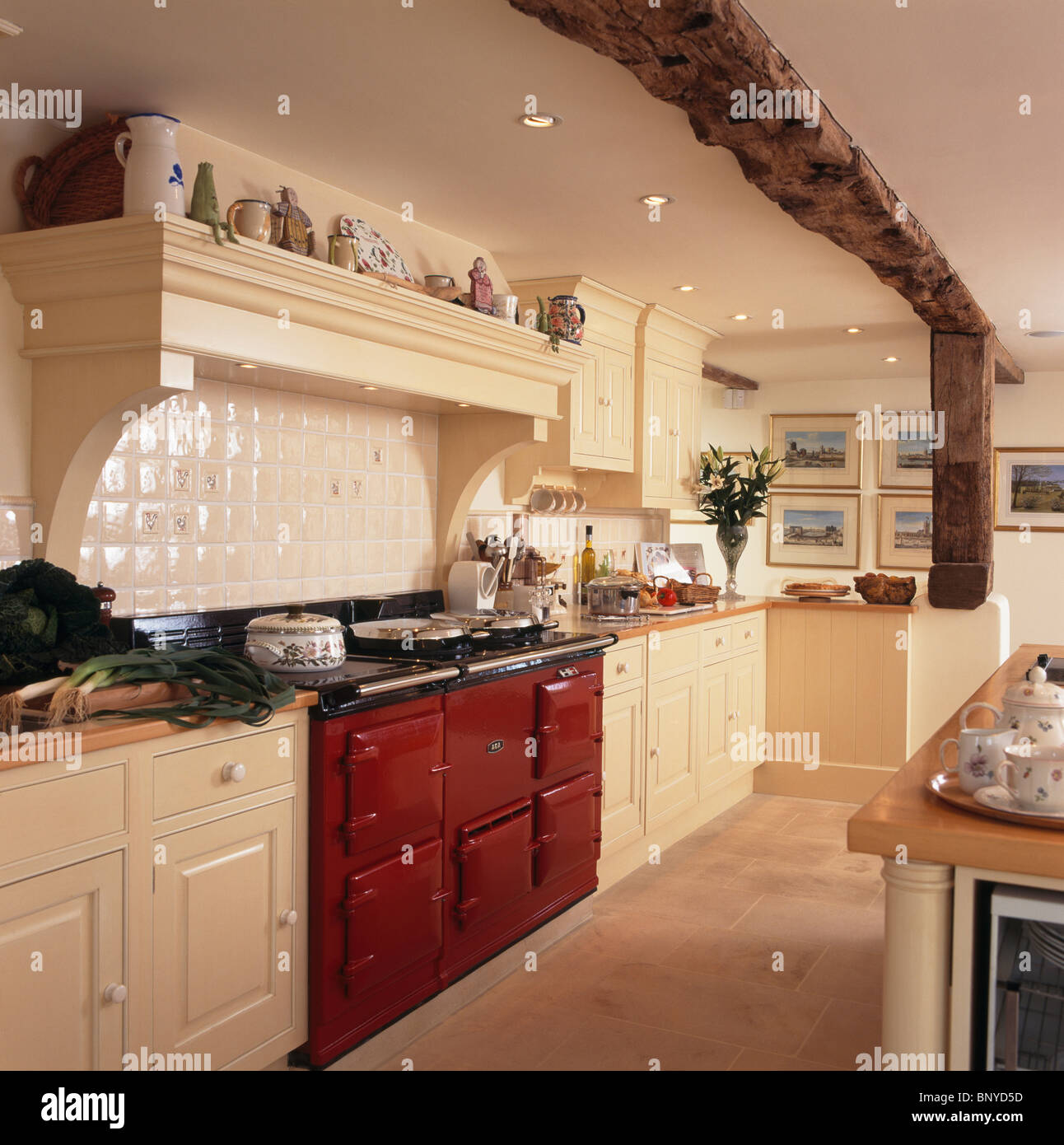 Red Aga Oven In Cream Country Kitchen With Large Rustic Wooden Ceiling Beam