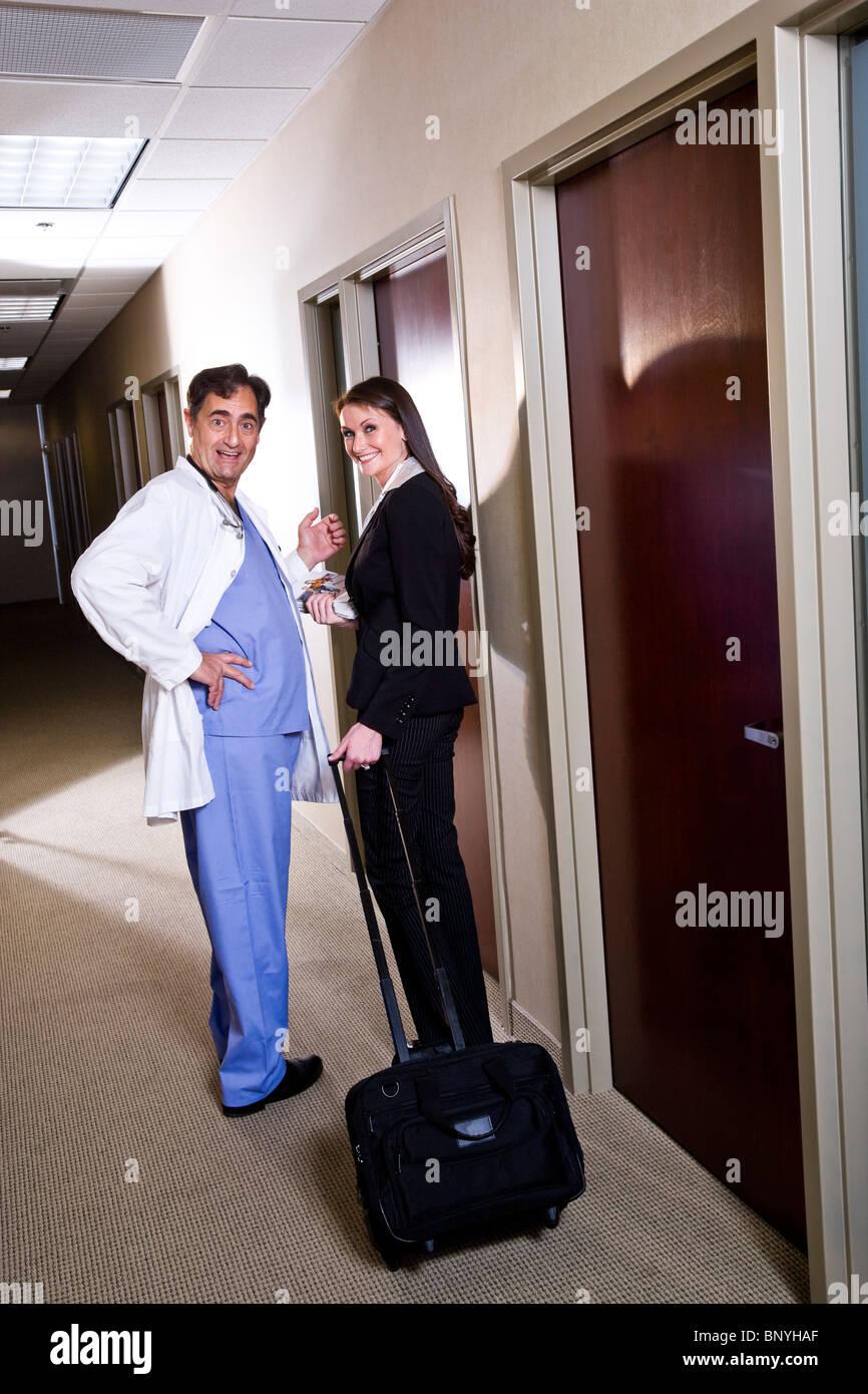 doctor talking pharmaceutical s rep in office corridor doctor talking pharmaceutical s rep in office corridor