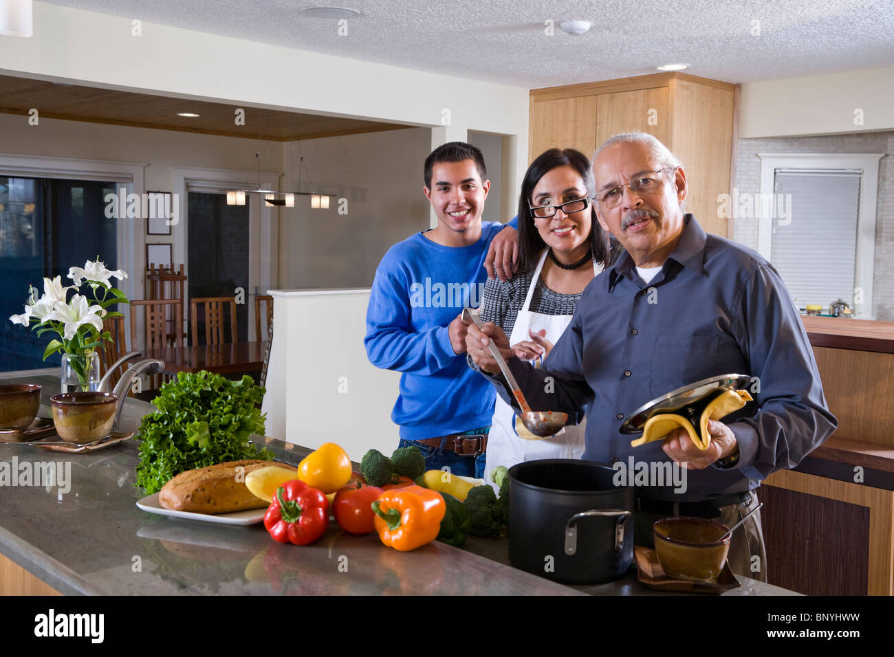Family cooking kitchen - Stock Photo Three Generations Hispanic Family Cooking Together In Kitchen At Home