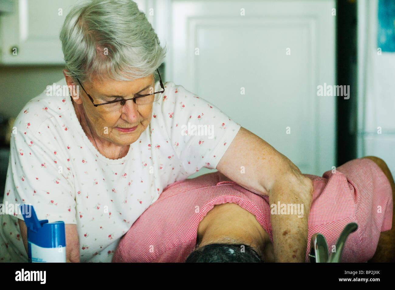 Old Woman Washing Old Manu0027s Hair At Kitchen Sink.